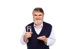 Viejo hombre con el vidrio de agua y de píldoras en manos Fotografía de archivo
