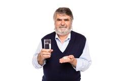 Viejo hombre con el vidrio de agua y de píldoras en manos Fotografía de archivo libre de regalías