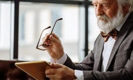 Viejo hombre con la mala vista que intenta descry una imagen en la pantalla de la tableta imagen de archivo libre de regalías