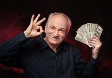 Viejo hombre con las cuentas de dólar Imagen de archivo libre de regalías