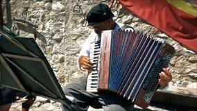 Viejo hombre con los vidrios que juegan el acordeón, apariencia vintage