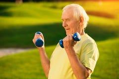Viejo hombre con pesas de gimnasia Foto de archivo libre de regalías