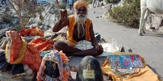 Viejo hombre con shivalinga del señor en la calle en la India