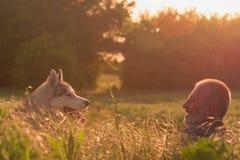 Viejo hombre con su perro en un campo en la puesta del sol Fotos de archivo libres de regalías