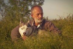 Viejo hombre con su perro en un campo en la puesta del sol Imágenes de archivo libres de regalías