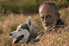 Viejo hombre con su perro en un campo en la puesta del sol Fotografía de archivo libre de regalías