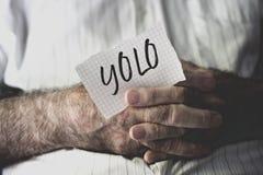 Viejo hombre con una nota con la palabra yolo Imagen de archivo libre de regalías