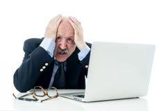 Viejo hombre de negocios abrumado y cansado que trabaja con el ordenador portátil que siente enojado en la oficina imagen de archivo libre de regalías