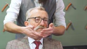 Viejo hombre de negocios barbudo que se sienta en la peluquería de caballeros en la silla que elige diseño del corte de pelo almacen de metraje de vídeo
