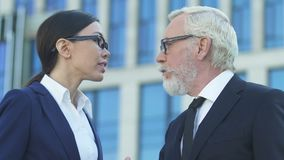 Viejo hombre de negocios que no escucha el empleado de sexo femenino joven, discriminación de género metrajes