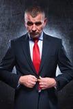Viejo hombre de negocios serio que desabrocha el suyo traje fotografía de archivo libre de regalías