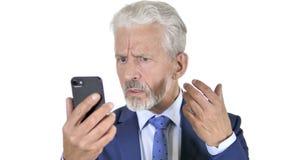 Viejo hombre de negocios Upset por la pérdida en Smartphone, fondo blanco almacen de metraje de vídeo