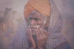 Viejo hombre de Rajasthani contra la perspectiva de sus camellos Fotografía de archivo libre de regalías