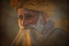 Viejo hombre de Rajasthani contra la perspectiva de sus camellos Foto de archivo libre de regalías