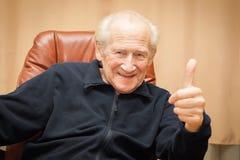 Viejo hombre de risa con los pulgares para arriba Foto de archivo libre de regalías
