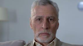 Viejo hombre descontentado que se sienta en el sofá y que mira la cámara, inseguridad social almacen de video