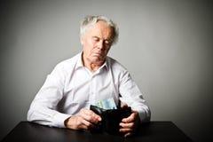 Viejo hombre en blanco y cartera con el euro veinte Fotografía de archivo