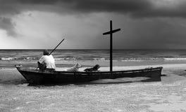 Viejo hombre en el barco de la ruina con mirada cruzada de madera en el océano Foto de archivo