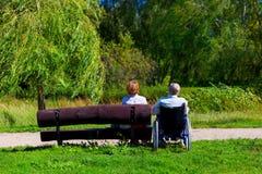 Viejo hombre en la silla de ruedas y la mujer joven en un banco Foto de archivo libre de regalías