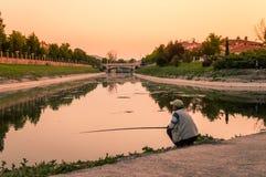 Viejo hombre en ropas casuales y un casquillo que pesca en el riverbank en la puesta del sol imágenes de archivo libres de regalías