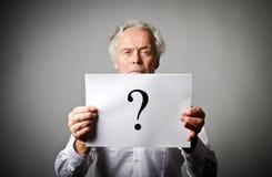 Viejo hombre en signo del blanco y de interrogación fotografía de archivo