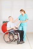 Viejo hombre en silla de ruedas en la fisioterapia Imágenes de archivo libres de regalías