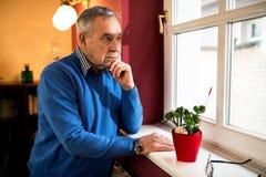 Viejo hombre enfermo mayor que mira a través de la ventana, permaneciendo solamente en casa foto de archivo