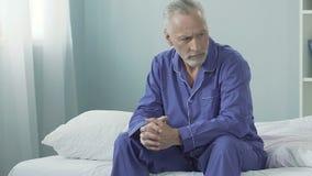 Viejo hombre enojado que se sienta en la cama, mirando alrededor sospechoso, descontentado, cambiante metrajes