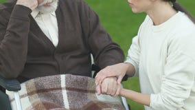 Viejo hombre favorable voluntario en la silla de ruedas, compasión para el enfermo, concepto de la caridad almacen de metraje de vídeo