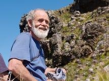 Viejo hombre feliz en montañas Fotos de archivo libres de regalías
