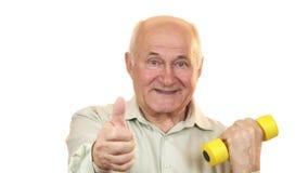 Viejo hombre feliz que muestra los pulgares para arriba que se resuelven con una pesa de gimnasia fotos de archivo