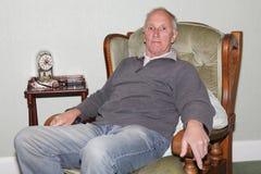 Viejo hombre feliz que se sienta en su butaca Imagen de archivo libre de regalías