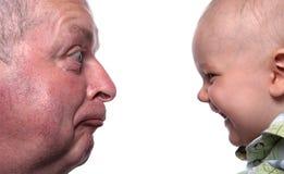 Viejo hombre gruñón y bebé feliz imagen de archivo libre de regalías