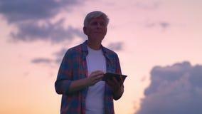 Viejo hombre hermoso en cortocircuito que mecanografía en la tableta, cielo asombroso rosado con las nubes en fondo almacen de metraje de vídeo
