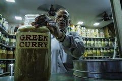 Viejo hombre indio con el tarro de cristal grande de curry caliente imagen de archivo