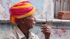 Viejo hombre indio en un turbante que fuma un cigarrillo almacen de metraje de vídeo