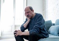Viejo hombre mayor infeliz triste que sufre de la pérdida de memoria y de Alzheimer que sienten presionados y solos foto de archivo