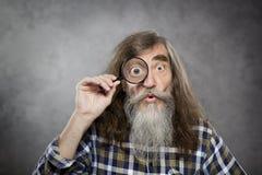 Viejo hombre mayor que mira con gla que magnifica del enfoque Fotos de archivo libres de regalías