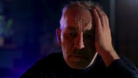 Viejo hombre mayor que se sienta por la chimenea con la expresión triste del thoughtfull almacen de video