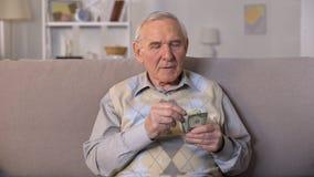 Viejo hombre presionado que se sienta en el sofá, sosteniendo billetes de banco de los dólares, inseguridad social almacen de video