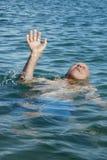 Viejo hombre que ahoga dolor del movimiento de la ayuda del mar Imagen de archivo libre de regalías