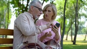 Viejo hombre que ayuda al smartphone envejecido del uso de la esposa, generación mayor usando el artilugio moderno fotografía de archivo