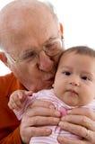Viejo hombre que besa al bebé lindo imagen de archivo libre de regalías