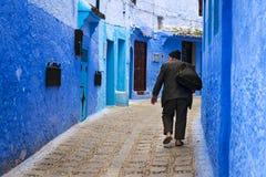 Viejo hombre que camina en una calle de la ciudad de Chefchaouen en Marruecos Foto de archivo