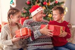 Viejo hombre que comparte los regalos de la Navidad con los niños Imagenes de archivo