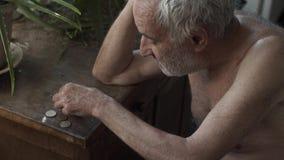 Viejo hombre que cuenta monedas en una tabla almacen de video