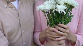 Viejo hombre que da las flores a la esposa feliz, celebración del aniversario, atención, cuidado almacen de metraje de vídeo