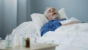 Viejo hombre que duerme en cama en la sala de hospital, antibióticos que se colocan en la tabla fotos de archivo libres de regalías