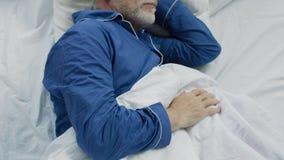 Viejo hombre que duerme en cama por la mañana, el tiempo de recuperación y el sueño sano fotografía de archivo