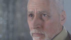 Viejo hombre que limpia el rasgón con la servilleta que mira el exterior lluvioso del tiempo, angustia almacen de metraje de vídeo